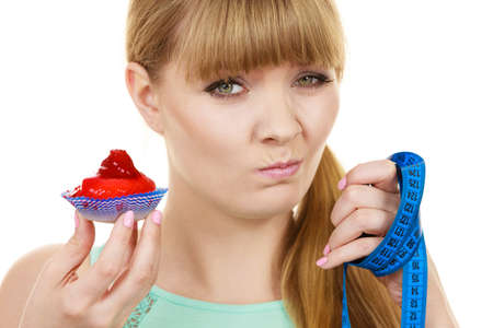 gluttony: Woman undecided with blue measuring tape holds in hand cake cupcake, trying to resist temptation. Weight loss diet dilemma gluttony concept. Stock Photo