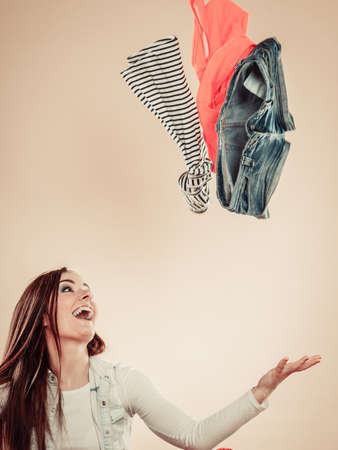 indecisive: Lifestyle and clothing love for fashion. Young female with outstretched arms throw colorful garment in air.