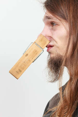 Man with clothespin clip peg on his nose. Young long haired guy feeling unpleasant odor stink. Bad smell concept.