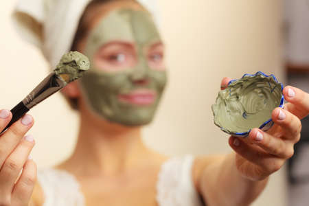 oily: Skin care. Woman applying with brush clay mud mask to her face. Girl taking care of oily complexion. Beauty treatment.
