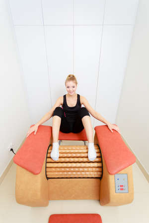 rid: Skincare, bodycare, wellness concept. Woman getting rid of buttocks cellulite on big roll machine. Healthy massage treatment in spa