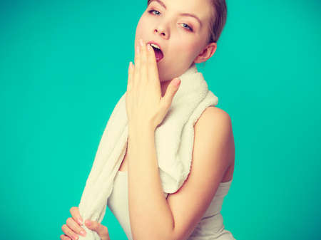 sleepiness: Tiredness, boredom concept. Sleepy woman placing hand on mouth yawning while holding towel on shoulder, studio shot on blue background