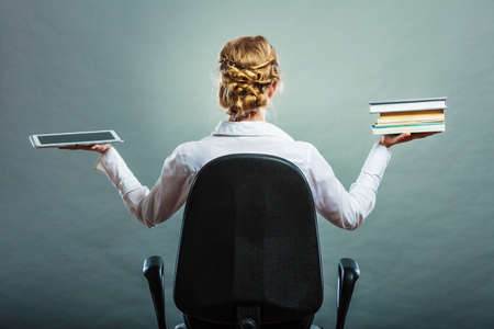 Ebook vs book. Woman sitting on chair holding traditional book and e-book reader tablet touchpad pc back view grunge background. Stock Photo
