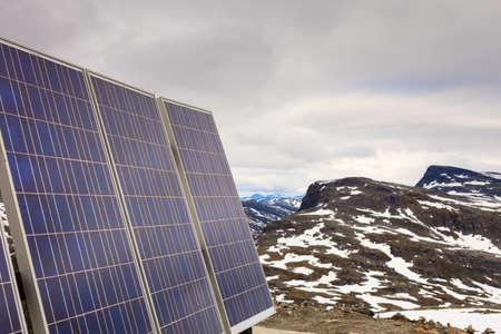 electricity generation: Renewable regenerative power and eco energy. Photovoltaic solar panel outdoor in norwegian mountains nature. System of electricity generation.
