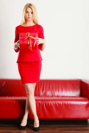 Occasions gifts people concept. Beautiful woman in full length with red gift. Young blonde lady wearing elegant outfit. Stock Photo