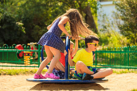 teeter: Joyful active childhood. Playful kids playing on playground. Children having fun in summer. Young tourists spending actively time. Stock Photo