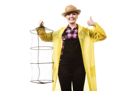 dungarees: Spinning, angling, cheerful fisherwoman concept. Happy woman in yellow raincoat holding empty fishing keepnet, having fun.