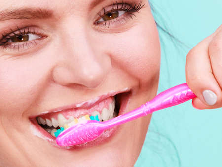 Woman brushing cleaning teeth. Girl with toothbrush close up. Oral hygiene. Blue green background Stock Photo