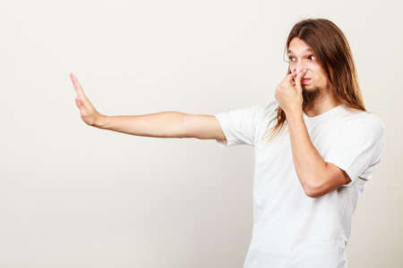 intolerable: Expression of very bad smell. Young long haired sweaty man making hand gesture. Sweating concept.