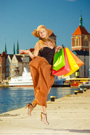 spending money: Spending money on sales, buying things concept. Fashionable woman happy jumping with shopping bags, wearing glamorous outfit and big sun hat