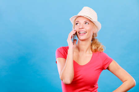 Technology, international talks, modern devices concept. Tourist woman in sun hat talking with someone through smartphone. Studio shot on blue background Stock Photo