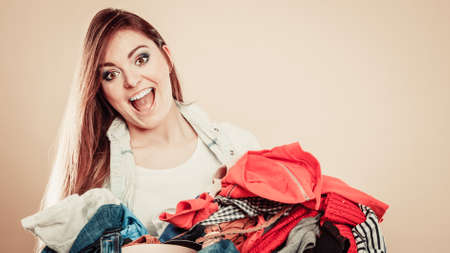 decide: Daily routine in household laundry decide what to wear. Young excited woman hold pile of colorful clothes. Stock Photo