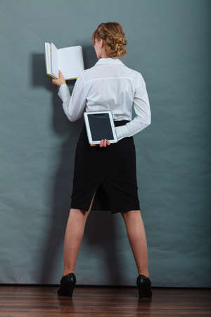 Ebook vs book. Woman female student holding traditional book and e-book reader tablet touchpad pc back view grunge background.