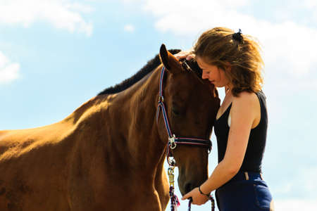 Taking care of animals, love and friendship concept. Jockey young girl kissing and hugging brown horse on sunny day Stock Photo
