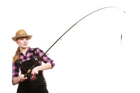 sportfishing: Spinning equipment, angling, cheerful fisherwoman concept. Focused woman in sun hat holding fishing rod hunting and fighting with fish on hook
