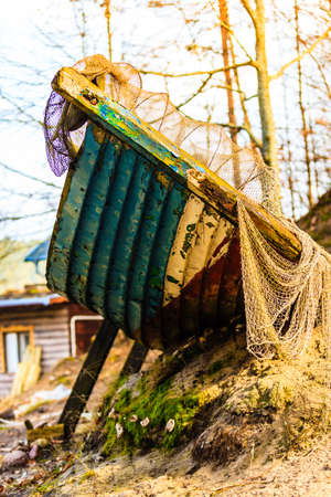 ship wreck: Vintage broken objects concept. Old, dirty piece of boat covered in net standing outside captured on sunny autumn day.