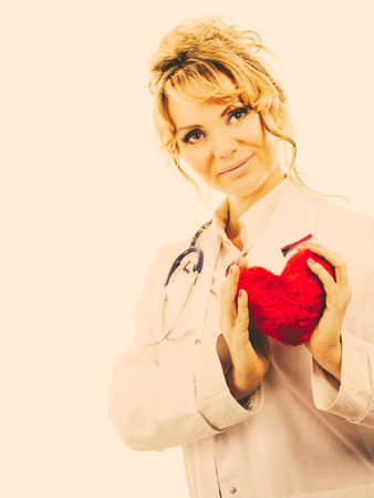 proffesional occupation: Periodic examinations. Cardiology concept. Female cardiologist holding red heart. Middle aged doctor with stethoscope and white medical apron uniform. Filtered.