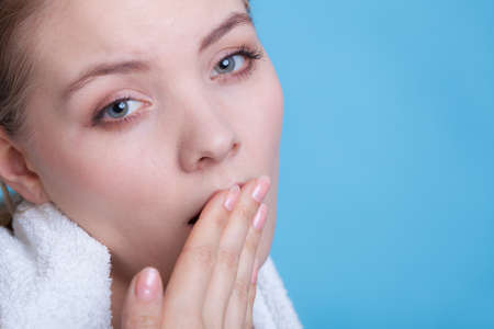 tiredness: Tiredness, boredom concept. Sleepy woman placing hand on mouth yawning while holding towel on shoulder, studio shot on blue background