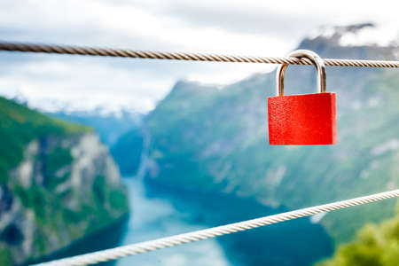 fidelidad: Tourism vacation and travel. Red love lock padlock on bridge and mountains, view over magical Geirangerfjorden from Flydalsjuvet viewpoint, Norway Scandinavia.