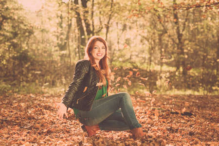 tossing: Relax leisure outdoor nature woodland concept. Cheerful ginger woman in park. Young redhead lady having fun with leaves tossing foliage around. Stock Photo