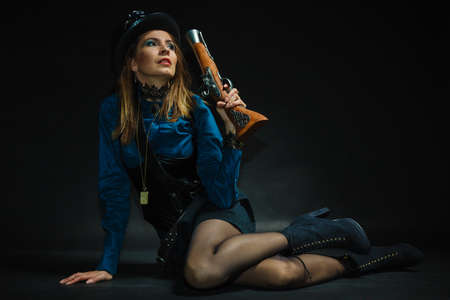blunderbuss: Subculture fashionable victorian elegant weapon concept. Steampunk girl armed and dangerous. Lady dressed in victorian fashion holding antique firearm aiming. Stock Photo