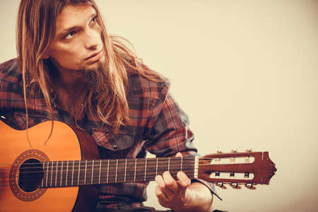 ballad: Young long haired guy playing guitar. Focused man practicing the game on the instrument.