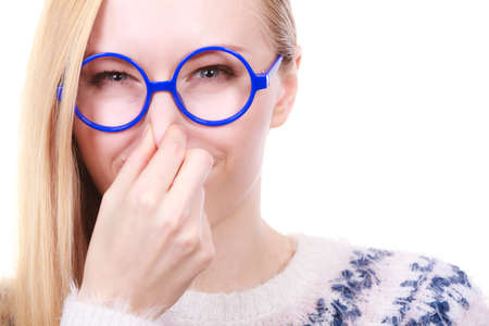 clogged: Stinky smells, clogged concept. Nerdy woman in big funny glasses holding nose smelling bad scent