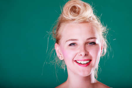 Hairstyling, feminity, female beauty concept. Beautiful smiling teenager young woman with pin up hair. Studio shot on green background. Stock Photo