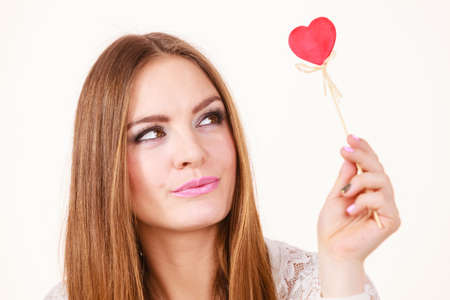 suspiciously: Valentines day gift concept. Beautiful woman holding and looking suspiciously at love sign, heart shaped wooden hand stick, studio shot on white background Stock Photo