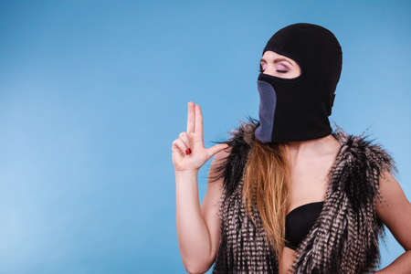 Woman sexy girl in balaclava black bra lingerie making gun gesture. Crime and violence on blue studio shot Stock Photo