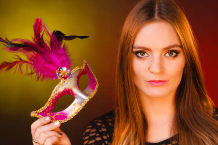 Party time, holidays, people and celebration concept. Woman long hair holds carnival mask close up Stock Photo