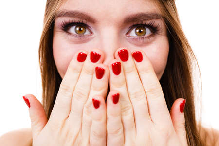 aghast: Fun, folly concept. Woman hiding her face behind hands with with red painted nails, crazy closeup.