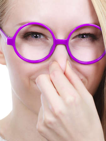 holding nose: Stinky smells, clogged concept. Nerdy woman in big funny glasses holding nose smelling bad scent