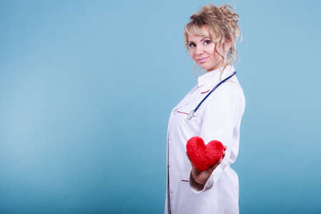 Help people concept. Medical idea of helping. Mature blonde happy doctor cardiologist with red heart enjoy her work. Middle aged woman wearing medic apron.