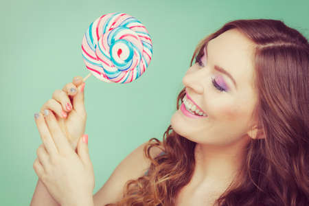 Woman attractive cheerful girl holding colorful lollipop candy in hand. Sweet food and enjoying concept. Studio shot green blue background, toned image