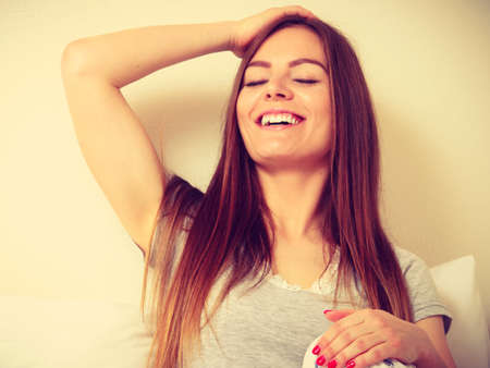 mornings: Happy mornings concept. Smiling young woman sitting in bed with one hand raised behind her head