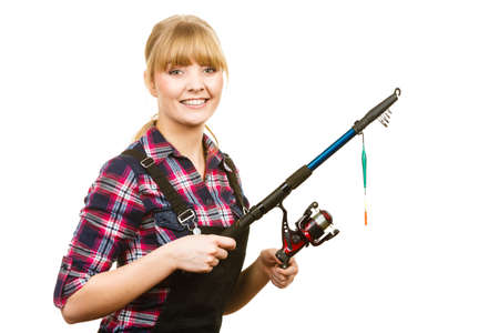 dungarees: Fishing concept. Attractive woman in dungarees, pink check shirt holding rod. Isolated background Stock Photo