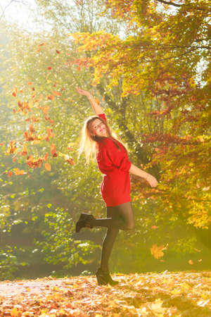Cheering girl with leaves. Young woman playing in autumnal park. Nature outdoor scenery leisure concept.