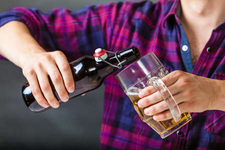 Alcohol liquor drinking relax party concept. Tapster fills stein from bottle. Young male bartender empties beer into glass. Stock Photo