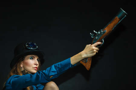 subculture: Subculture fashionable victorian elegant weapon concept. Steampunk girl armed and dangerous. Lady dressed in victorian fashion holding antique firearm aiming. Stock Photo