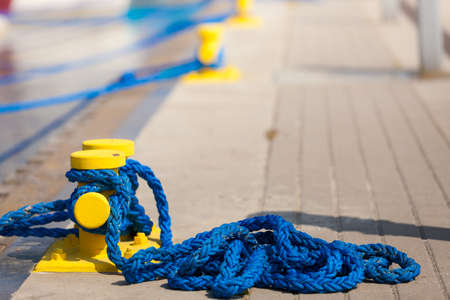 Shipping objects concept. Sailing ropes tied around yellow marina pins. Outdoor shot on sunny day. Stock Photo