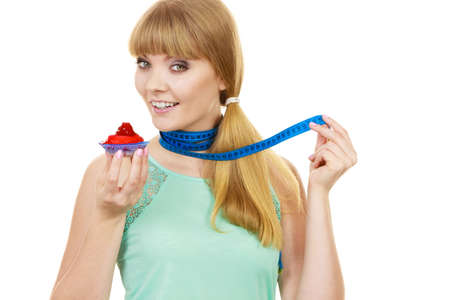 Woman smiling girl with blue measuring tape holds in hand cake cupcake. Weight loss dieting or sweet food and happiness concept.