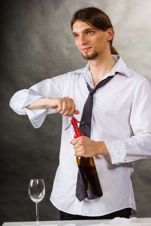 Winery serving tasting alcohol liquor concept. Waiter opens wine bottle. Young male sommelier pulls out cork.