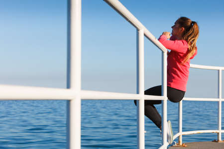 Woman resting after doing sports outdoors. Fitness girl in sportswear sitting on pier relaxing looking at horizon back view