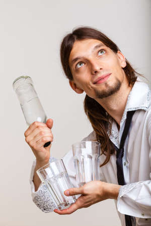 Alcohol drinking liquor party relax concept. Cheerful barman filling glasses. Young male holding bottle pouring beverage.