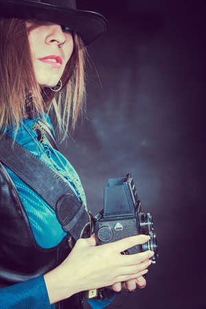 subculture: Photography and retro style. Young vintage attractive girl holds old aged camera. Steampunk photographer taking photo. Stock Photo