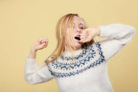 cansancio: Tiredness, too much work at school concept. Sleepy yawning blonde teenage woman in jumper feeling exhausted