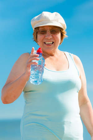 Summer, vacation, active retired people. Happy smiling old woman drinking mineral water from plastic bottle outdoor, enjoying summer sunny day Stock Photo