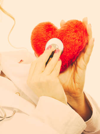 Medical examination of cardiology. Cardiologist with heart and stethoscope. Female doctor in white uniform makes measurement heartbeat. Filtered.
