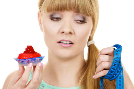Woman undecided with blue measuring tape holds in hand cake cupcake, trying to resist temptation. Weight loss diet dilemma gluttony concept. Stock Photo